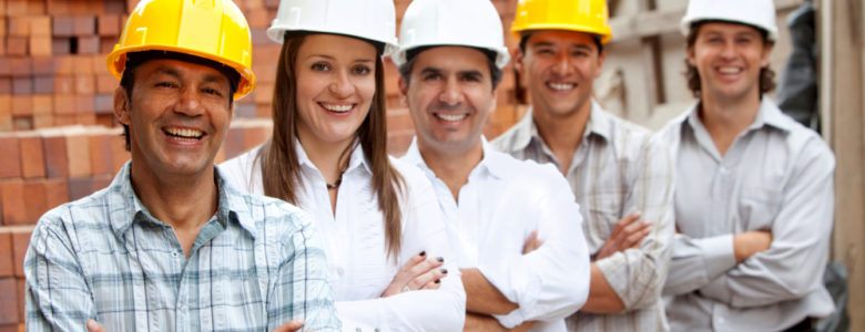 Group of architects and engineers at a construction site smiling